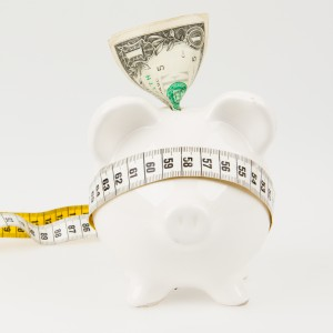 White piggy bank with measuring tape on white background
