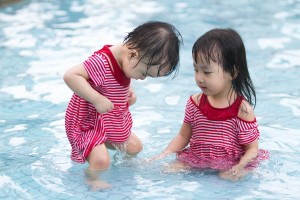 Two Little Sisters Playing in Water in Swimming Pool